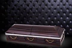 在灰色豪华背景的闭合的木棕色石棺 小箱,在皇家背景的棺材 库存照片