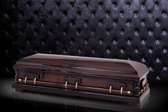 在灰色豪华背景隔绝的闭合的木棕色石棺 小箱,在皇家背景的棺材 图库摄影