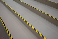 在灰色走道的工业镶边路或步警告 免版税库存图片