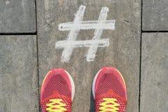 在灰色边路的Hashtag标志有在运动鞋的妇女腿的,顶视图 免版税库存照片