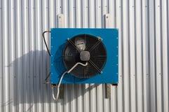 在灰色金属墙壁安装的小蓝色工业冷却装置的正面图 免版税库存照片