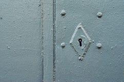 在灰色门的生锈的匙孔 库存照片