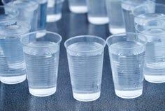 在灰色隔绝的许多塑料杯子 免版税库存照片