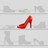 在灰色鞋子背景的红色鞋子  免版税库存图片