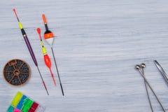 在灰色,木桌套钓鱼的项目,坠子,浮游物,钓鱼线,在中心有做广告的一个地方 图库摄影