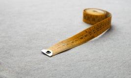 在灰色织品的黄色测量的磁带 库存图片