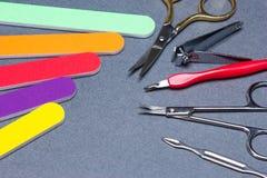 在灰色织地不很细背景的各种各样的修指甲工具 免版税库存照片