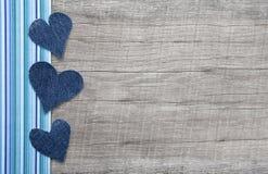 在灰色破旧的别致的木背景的牛仔布心脏 免版税库存照片