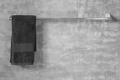 在灰色水泥墙壁上的不锈钢毛巾有毛巾的在卫生间里 免版税库存图片