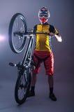 头戴在灰色ba的一个专业骑自行车者的画象一件盔甲 免版税图库摄影