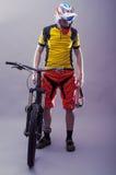 头戴在灰色ba的一个专业骑自行车者的画象一件盔甲 免版税库存图片