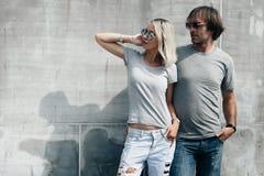 在灰色T恤杉的夫妇在街道墙壁 库存图片