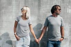 在灰色T恤杉的夫妇在街道墙壁 免版税库存照片