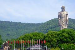 在灵山的盛大菩萨雕象有在前面的旗子的 库存照片