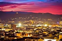 在灼烧的天空黄昏的格拉茨市中心鸟瞰图 库存照片