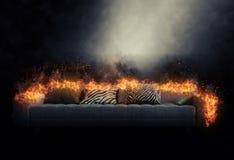 在灼烧的火焰吞噬的沙发 库存照片
