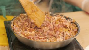 在炖在煎锅期间,厨师混合切得很细的猪肉牛排和葱 图库摄影