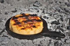 在炭烬和灰的一个生铁长柄浅锅被烹调的可口阿根廷普罗卧干酪毛线乳酪Provoleta ?? 免版税库存图片