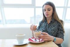 在点心的焦点 一名美丽的妇女吃在一个现代和清淡的咖啡馆的一个开胃,美丽的点心 库存照片