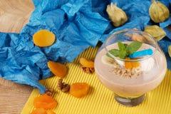 在点心玻璃的水果的圆滑的人与在黄色和蓝色背景的秸杆 鸡尾酒用杏干,冰淇凌 库存照片