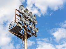 在点燃的帆柱的十二盏强有力的聚光灯在反对天空蔚蓝的体育场与白色云彩在一天 库存图片