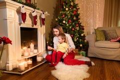 在点燃蜡烛的地毯的妈妈和儿子夫妇 库存图片