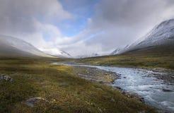 在点燃部分和积雪的山的云彩和阳光的秋天风景 库存图片