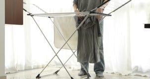 在烘干机的庄稼妇女垂悬的衣裳在家 股票录像