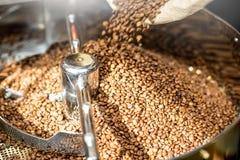 在烘烤器机器的咖啡豆 库存图片