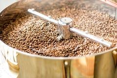 在烘烤器机器的咖啡豆 库存照片
