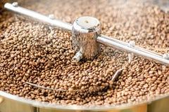 在烘烤器机器的咖啡豆 免版税库存图片