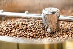 在烘烤器机器的咖啡豆 免版税库存照片