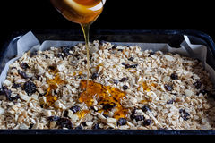 在烘烤盘子的格兰诺拉麦片用从边的蜂蜜 库存图片