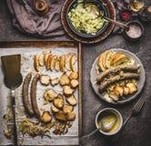 在烘烤盘子的油煎的香肠在板材服务用白色凉拌卷心菜沙拉和芥末垂度在土气厨房用桌上,顶视图 德语 库存图片