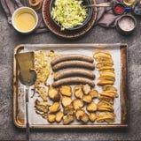 在烘烤盘子的油煎的香肠用白色凉拌卷心菜和芥末浸洗 免版税库存照片