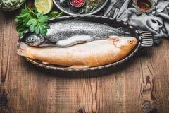 在烘烤盘的两条未加工的鳟鱼鱼与在土气木背景,顶视图的成份 免版税库存照片