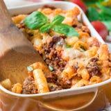 在烘烤盘的意大利通心面博洛涅塞,面团砂锅用肉末,西红柿酱和乳酪,正方形 免版税库存图片