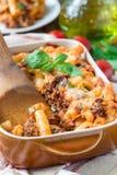 在烘烤盘的意大利通心面博洛涅塞,面团砂锅用肉末,西红柿酱和乳酪,垂直 免版税库存图片