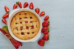 在烘烤盘的自创大黄草莓饼在与赠送阅本空间的灰色厨房用桌上 素食饼 库存照片