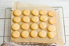 在烘烤纸和电线支架的橙色黄油曲奇饼 库存照片