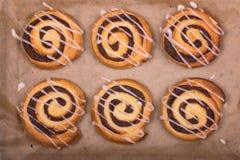 在烘烤羊皮纸的新近地煮熟的桂香漩涡小圆面包 免版税库存照片