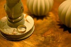 在烛台旁边的一只金戒指 库存照片