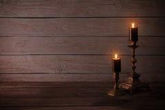 在烛台的黑灼烧的蜡烛在老木背景 库存图片