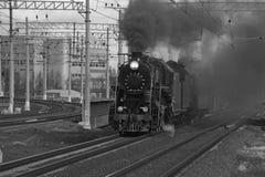 在烟云的黑白老蒸汽火车乘驾由铁路 图库摄影
