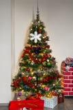 在烟囱旁边的装饰的圣诞树 免版税库存图片