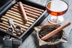 在烟灰缸、打火机和科涅克白兰地的雪茄 库存照片