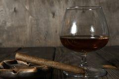 在烟灰缸和一杯的雪茄在橡木的科涅克白兰地构造了桌 免版税库存图片