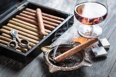 在烟灰缸和科涅克白兰地的灼烧的雪茄 库存照片