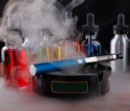 在烟灰缸和vape液体的电子香烟在黑背景的蒸气内 免版税图库摄影