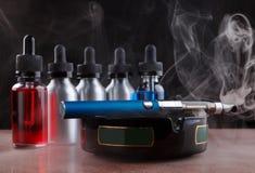 在烟灰缸和vape液体的电子香烟在黑背景的蒸气内 库存照片